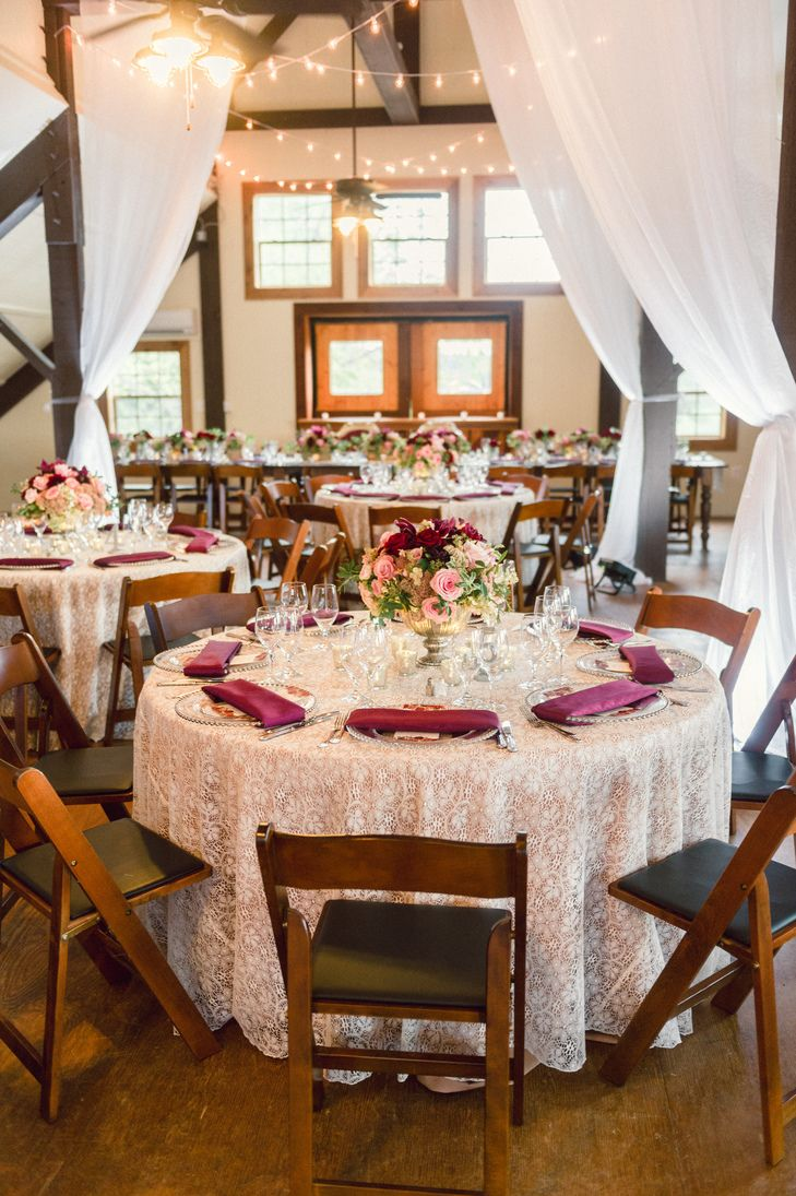 The barn reception at Stone Tower Winery was draped with white linens and illuminated with string lights. The alternating round and farmhouse tables were set with lace overlay tablecloths and lace table runners.