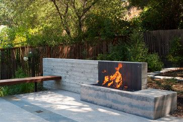 Wall of board formed concrete acts as a backdrop to Ipe' bench and custom cast concrete fire pit. Fire pit has corten steel backing.