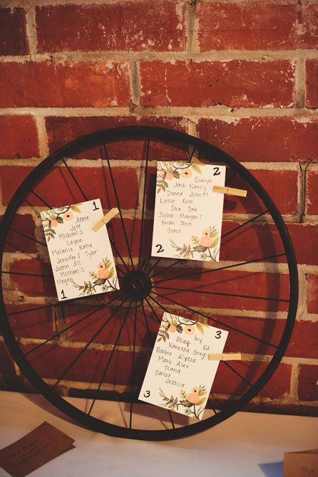 Seating chart in aged bicycle wheel for Winter Park romantic spring farmers market wedding | Photo: Jason Mize Photography