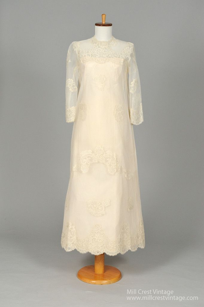 Designed in the 60's, this fabulous vintage wedding gown is done in an off white lace embroidered net over a taffeta lining. The bodice offers a lace embroidered scalloped jeweled neck line and long s