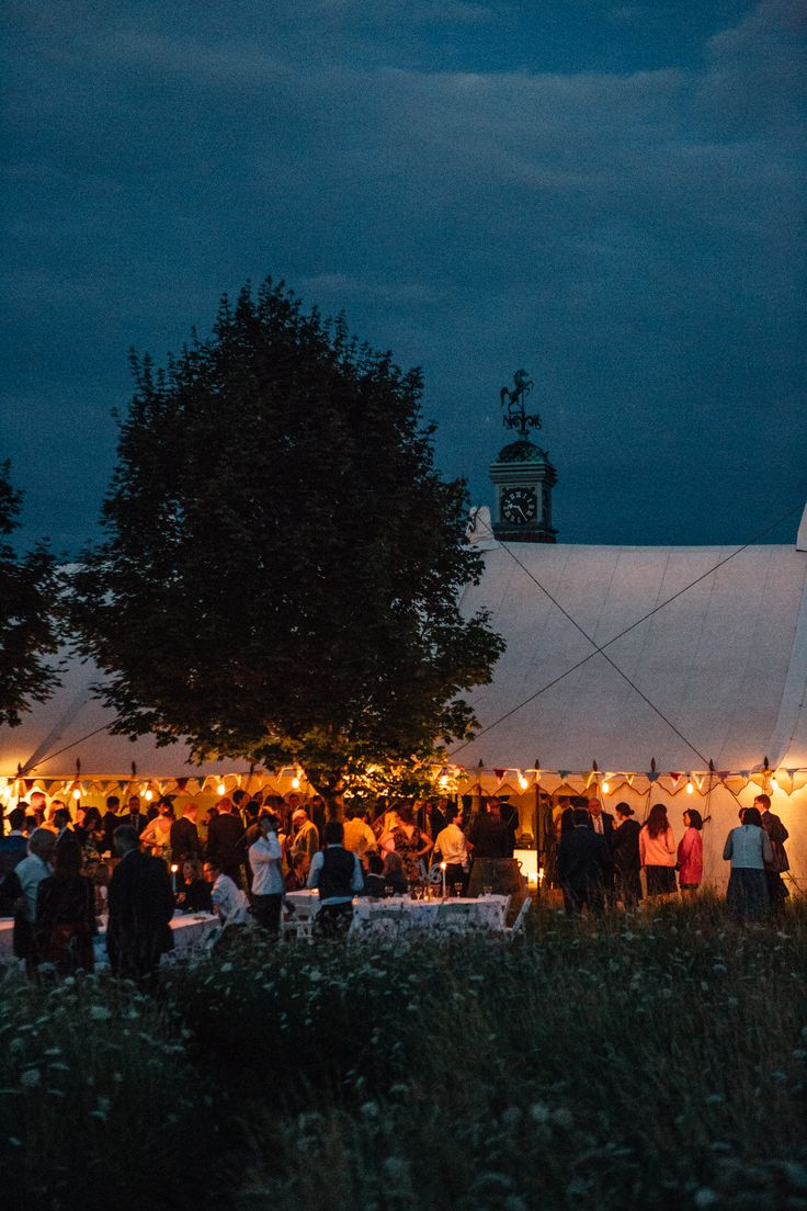 40' x 100' Traditional Canvas Pole Tent by night with festoon lighting.