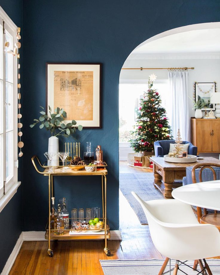 Instagram photo by @em_henderson • 9,439 likes - navy blue paint wall in dining room. Christmas tree and gold bar cart - holiday decor.