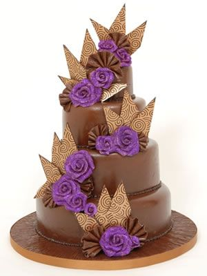 3 tier dark chocolate cake with dark purple edible glitter roses and gold swirl transfer sheet shards.