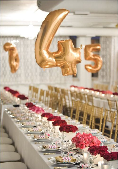 Gold balloon table numbers punch up a formal wedding