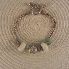 Pleine tendance pour ce bracelet en maille argentée,grosse perle tonneau strassée, 4 rondelles de pierre amazonite vert d'eau et 2 superbes perles blanches céramique à facettes et fermoir toggle.