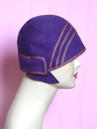Art Deco cloche hat. These bell-shaped hats were in fashion in the 1920s, typically made of felt. This hat covers and compliments the boyish hair cuts that they had during this time. The deep colour works well with the simplicity of the arced line detailing.