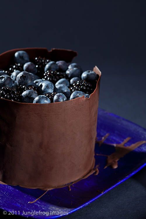 bolo de ganache de chocolate com frutas e  coberto por uma fatia fina de chocolate