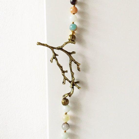 Collana realizzata con perline di pirite, amazzonite e bronzo. Nella parte laterale alta è inserito un ramoscello di bronzo e il ciondolo è un cuore sfaccettato di diaspro verde.