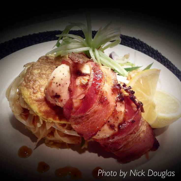 Padthai with bacon wrapped chicken breast .