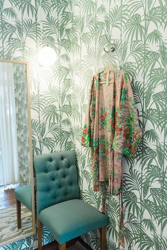 Dressing room with tropical wallpaper and a gold mirror