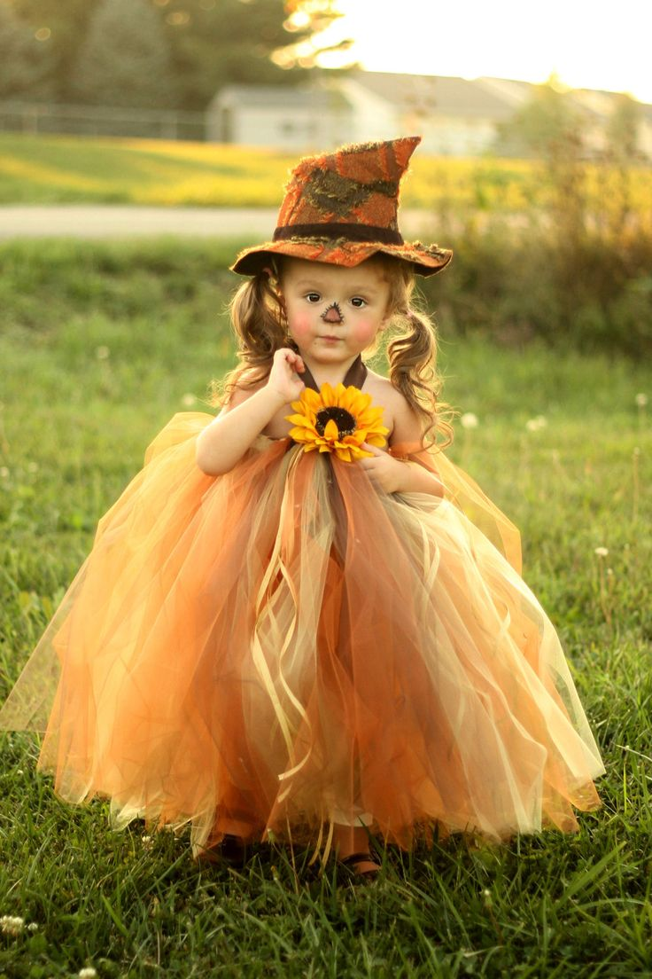 An adorable tutu dress made out of cooper, chocolate brown and yellow tulle finished with raffia and a sunflower and a brown satin halter tie. With the matching little hat, she is sure to be the cutest little scarecrow ever