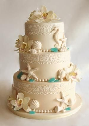 beach wedding cake. This three tier cake was covered in ombre beige fondant. The band at top of each tier caw done with royal icing using a custom made stencil to match the wedding invites. Orchids and seashells were made in gumpaste, and for the sea glass isomalt was used. by graciela
