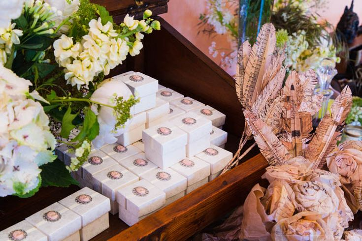 Favor boxes inside a school table and surrounded with natural and paper flowers. The music feathers also gave a nice touch!