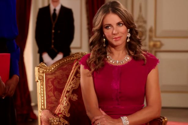 We can't decide who looks more beautiful here - Elizabeth Hurley or our Florence cushion in claret and gold velvet. As featured in The Royals on E.