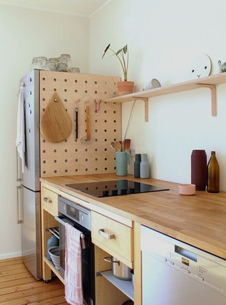 A DIY wooden pegboard in the kitchen of illustrator/graphic designer Swantje Hindrichsen created from used Ikea components.
