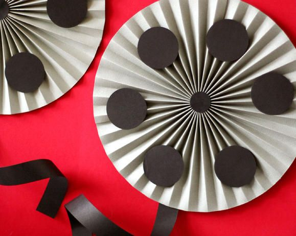 accordion circles turned into movie reels for a dramatic backdrop by simply adding a few circle punches and black ribbon