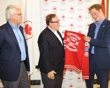 Prince Harry is presented an official 2012 Canadian Olympic Team jacket by Canadian Olympic Committee President Marcel Aubut (centre) while Canada's High Commissioner to the United Kingdom, Gordon Cam