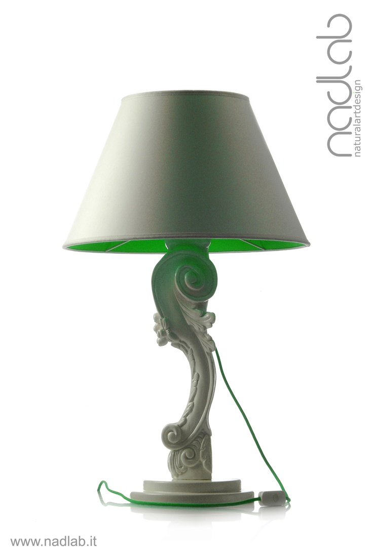 Bucefalo white/green (light OFF)  The base and the body of the lamp in wood are hand-carved.  The lampshade is made of PVC and coated in white chinette lined in green lycra.  Decorated in white gloss.  Customizable on request.