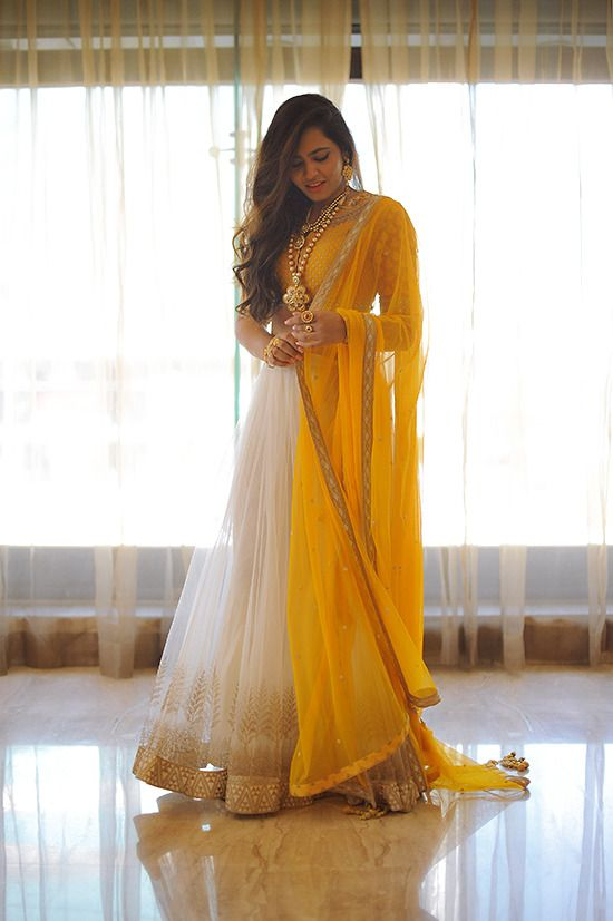 Love this white, gold and yellow lehenga and dupatta. The looks is completed with a statement necklace and wavy hair. Indian bridal fashion.