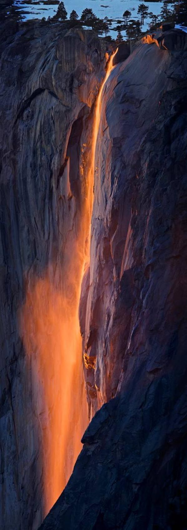 """Lavafall at Yosemite -This is nature's version of the old man-made Yosemite Fire Fall. During the winter in Yosemite, coming off of El Capitan, there is an almost nonexistent waterfall called """"Horsetail Falls."""" Many maps don't even have it marked. During the last two weeks in February, IF there is water trickling over the edge, and IF it is clear at sunset the setting sun will turn this waterfall into a stream of molten fire. The waterfall lights up like molten lava due t"""