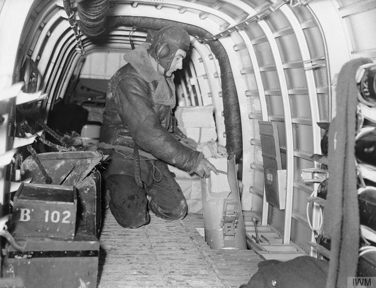 "One of the aircrew of an Armstrong Whitworth Whitley Mark V of a Detachment of No. 102 Squadron RAF at Villeneuve/ Vertus, France, demonstrates how propaganda leaflets are dropped through the flare chute on leaflet-dropping (""Nickelling"") sorties. ~ BFD"