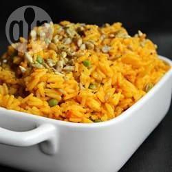 Reis mit Kurkuma und Gemüse - Diese einfache Reisbeilage mit Zwiebeln, Erbsen und Karotten bekommen durch den Kurkuma eine tolle gelbe Farbe. Sonnenblumensamen geben dem Reis Biss. @ de.allrecipes.com