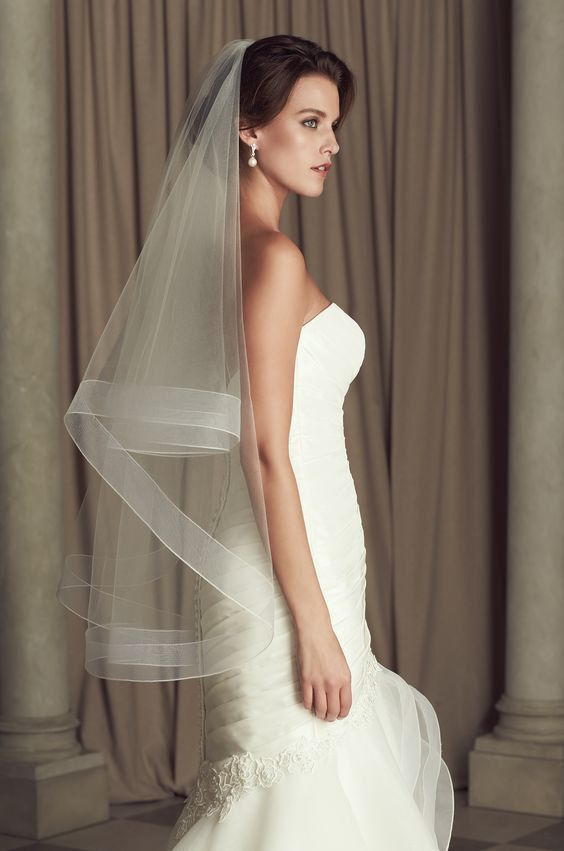 Niagara - Two Tier Couture Bridal Veil with 2 horsehair edging. This elegant veil made from soft tulle and crafted in our studio in Maine. Available in White, Ivory, Blush, Pink or Champagne shades. This veil fall somewhere in-between, such as waist length and fingertip length. Since this veil comes with the comb the length will depend not only on your height, but also on where, on your head you place comb. If you wear your veil forward, towards the front of your head, it will take a few…