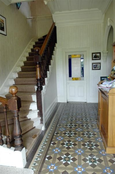 The original Minton-tile floor in the front entrance, with the original staircase. The house has remained relatively unchanged during more than 140 years.