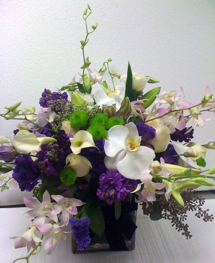 Exotic centerpiece Dendrobium #orchids, mini Calla Lily, Phaelanopsis orchids, purple #liseanthus and green button pompoms.