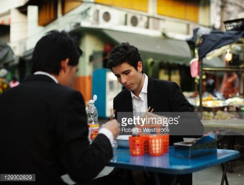 Stock Photo : Businessmen eating lunch together outdoors