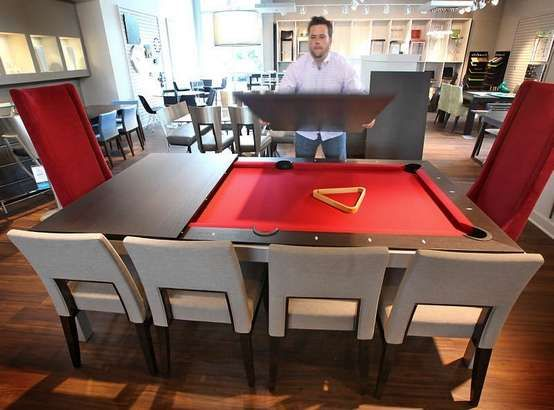 Dustin Polster, assistant manager of Houseworks, shows the versatile formal dining-room table that converts to a regulation-size pool table by simply removing the leafs. The Northeastside store has updated its decor and merchandise.