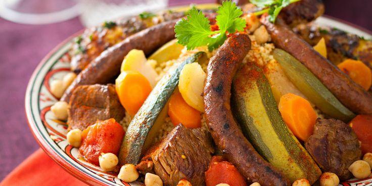 COUSCOUS ROYAL (Pour 6 P : 800 g d'épaule d'agneau, 6 pilons de poulet, 6 merguez, 700 g de graines à couscous, 200 g de pois chiches cuits, 1,5 kg de légumes (carottes, tomates, navets, courgettes), 2 oignons, 2 c à s de concentré de tomates, 1 côte de céleri, 1 petit bouquet de persil plat, 2 c à s d'épices à couscous, 4 à 6 c à s d'huile d'olive, 30 g de beurre, sel, poivre)