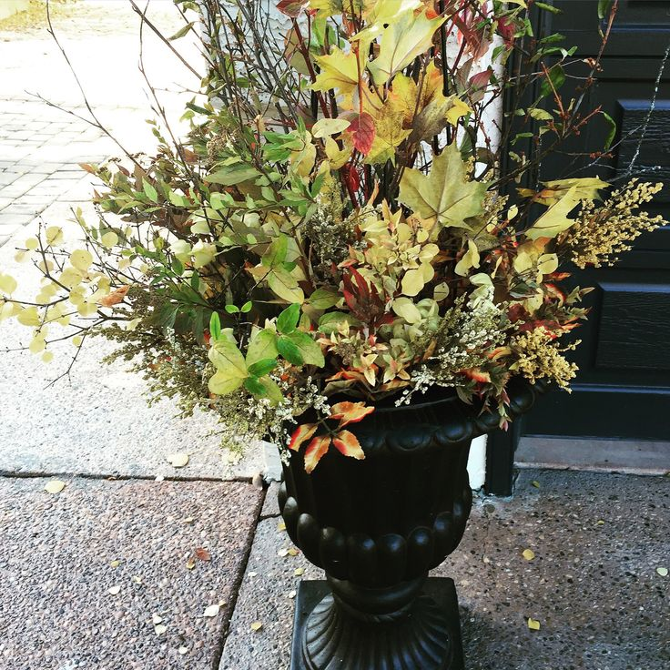 black outdoor urn with real and artificial Autumn florals