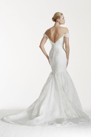 You'll be an unforgettably chic bride as you say I Do in this bonded lace v-back gown!  Fitted off-the-shoulder bodice features anatomical, contour seaming detail for a dramatic bridal look.  Sultry deep-v back with button back detail for added allure.  Flared trumpet skirt takes this bonded lace dress to the next level.  Sweep train. Sizes 0-26W.  Available online and in select stores in Soft White. Plus sizes available for special order only in store and online.  Fully lined. Imported