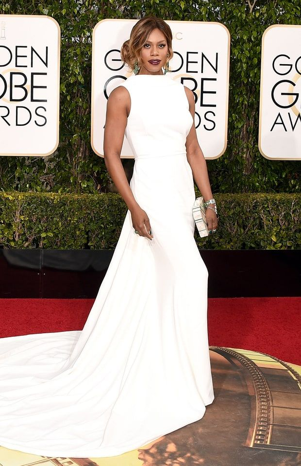 Golden Globe Awards 2016 - Laverne Cox in Elizabeth Kennedy | Flaunting her exquisite taste, Laverne wore a very elegant ivory dress that shaped her body to perfection. High neck, long tail accompanied with emerald jewelry and burgundy lipstick. How to make this outfit to be even more gorgeous? An up style hair and Californian wavy strands.