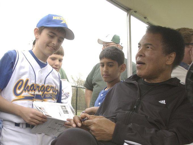 Muhammad Ali  hands an autograph to John DiLaura, 13, from Clinton Township on April 24, 2004... Doug Allen/The Battle Creek Enquirer
