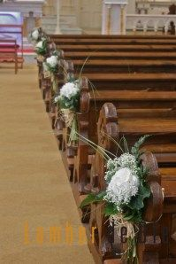 Pew decorations for a church wedding with white Hydrangea flowers and natural green