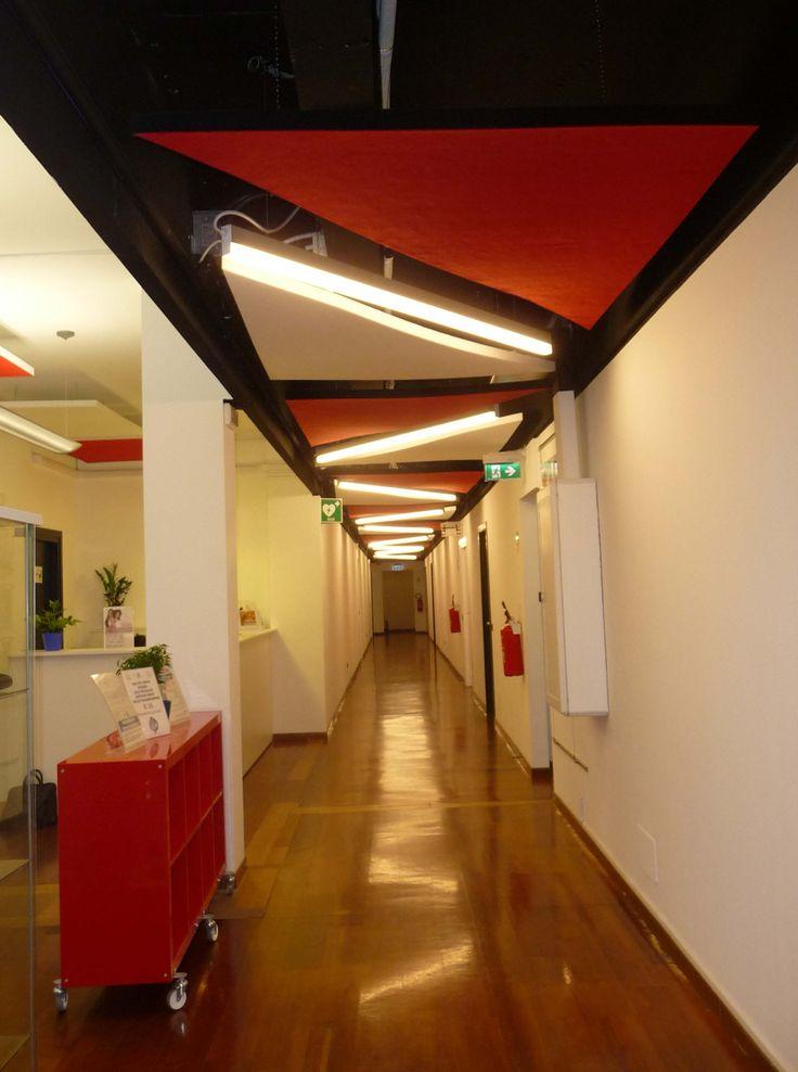 """Il modo in cui i plafoni sono stati trattati ha modificato la percezione dell'intero spazio. Il soffitto che solitamente all'interno di un ambiente, spesso viene sottovalutato, in questo intervento è stato considerato come la """"quinta parete"""".  La scelta della colore rosso (tessuto rosso di rivestimento) e della forma triangolare dei pannelli posizionati lungo i corridoi ha creato dinamicità in tutto l'ambiente."""