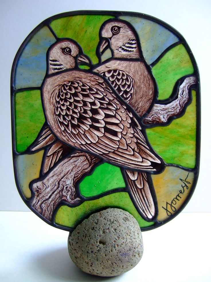 Two turtle doves representing love. Hand painted and kiln fired and in a bespoke stand made from a pebble.