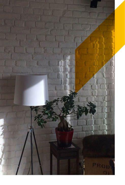 Un salón con paneles de ladrillo macizo blanco y que entre la luz