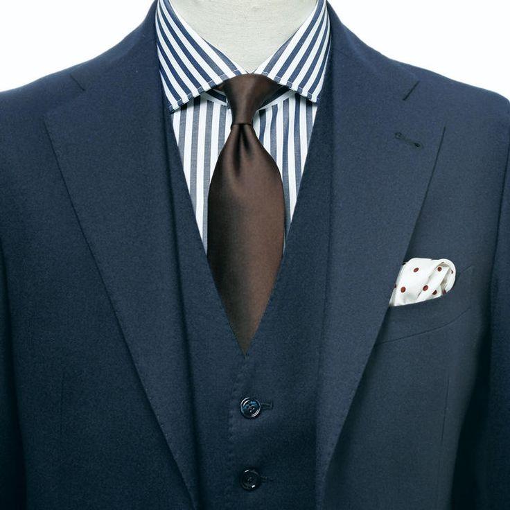 精悍にして貫禄ある、3ピーススーツとストライプシャツ。胸元は手堅く定番配色でまとめつつ、ドット柄チーフで軽快さを引き出した。さりげない大人の余裕が漂う。チーフ:ポール・スチュアート(6,500円)