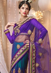 Purple and shaded teal blue net lehenga style saree designed with resham, sequins, stone, zari, beads and patch border work. Matching purple art silk blouse is available with this, blouse shown in the image is just for photography purpose.(Slight variation in color and patch patti pattern is possible.)