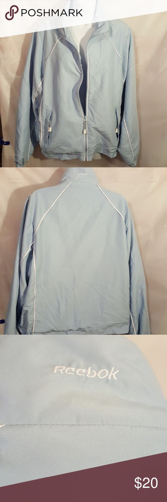 """Reebok Womens Windbreaker XL This is a womens Reebok windbreaker, lightweight.  Light blue with white pipping.  Zipper front closure. Long sleeved. Material is polyester. Size XL.  Measurements Shoulder to shoulder. 18"""" Chest. 24 1/2"""""""" Lengrh.   23 1/2"""" Reebok Jackets & Coats"""