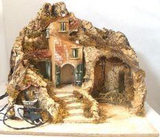 Scena presepe realizzata a mano secondo la tradizione napoletana. Nel paesaggio c''è la capanna (con luci), un gruppo di case (con luci) ed una fontana (con pompa ad acqua funzionante). Dimensioni: base 45X43 cm, altezza scena cm 41.