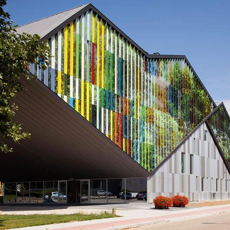 From certain angles this performance centre in Belgium has a colourful stripy facade, but from others it appears camouflaged amongst the surrounding trees