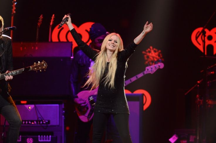"""I wish I could hug everybody."" Avril Lavigne stretches wide during a performance on Dec. 9 in Chicago"