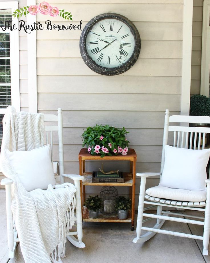 Cozy white rockers on the back porch with comfortable accessories -- neutral throw and white pillows...along with a $5 bar cart from a yard sale, a metal clock, and pretty flowers | The Rustic Boxwood | porch decor, porches, back porch, white, rocking chairs, bar cart, vintage, metal, decorating ideas, home decor, farmhouse style