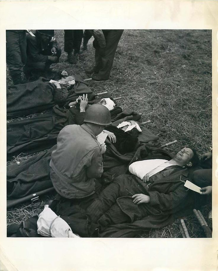 1944- French civilians, wounded during the Normandy battles on June 19, 1944, lie on stretchers on the ground behind the lines, where they are treated by U.S. Army medical corpsmen.