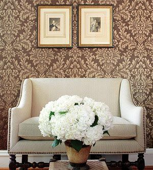 Damask walls and nail head couch.