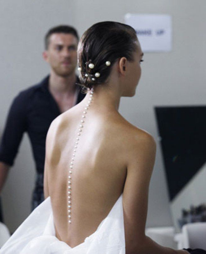 Pearls, Chanel backstage.   I wouldn't them that far, but they would be pretty down just a bit if you have a low back dress~